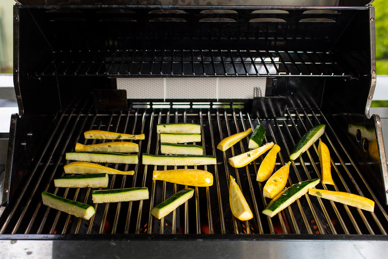 Zucchini and yellow squash placed on a grill.