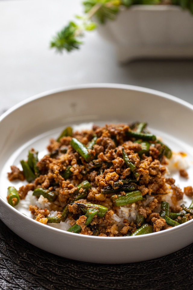 White bowl with ground pork, green beans and rice.
