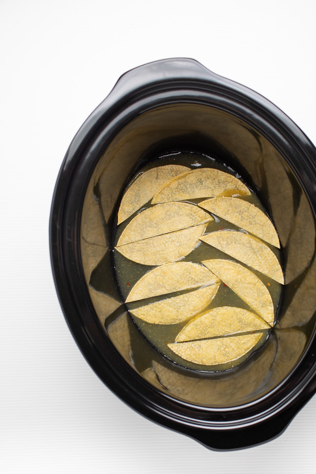 Tortillas lining the bottom of the crockpot.