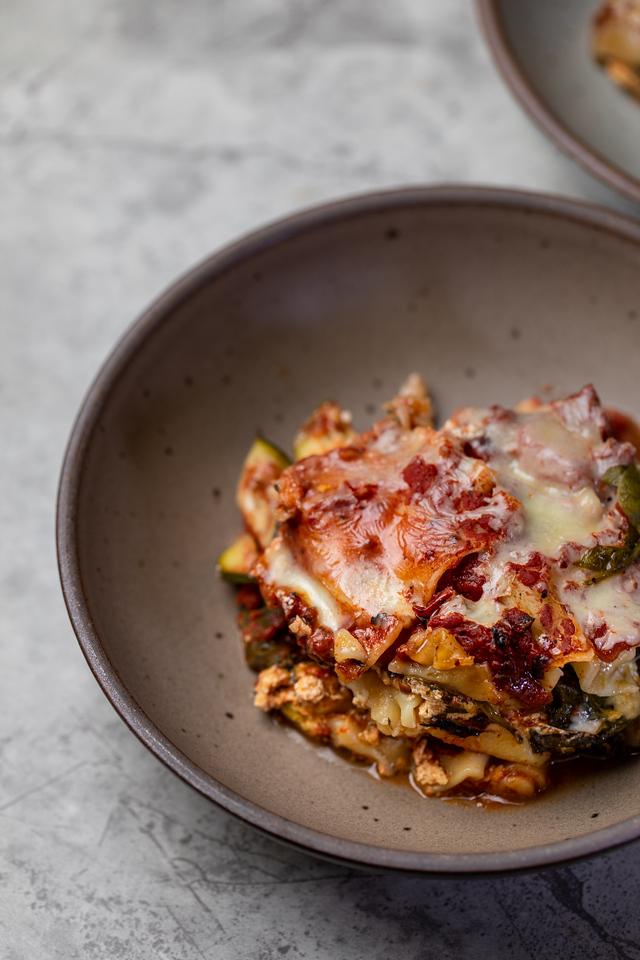 Close up of cheesy lasagna in a brown bowl.