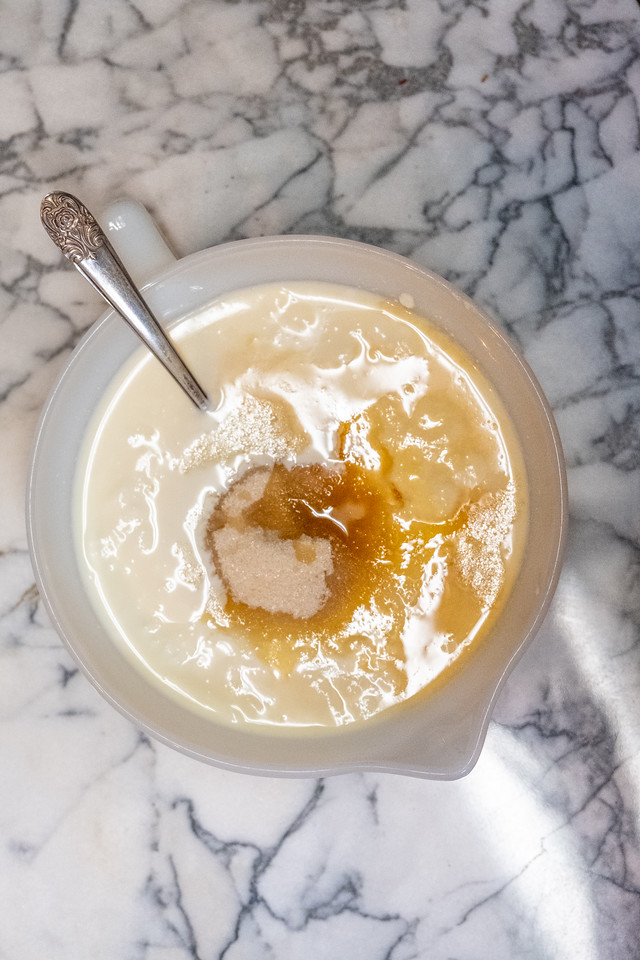 Bowl of yogurt with half and half, sugar, honey and vanilla extract on a marble background.