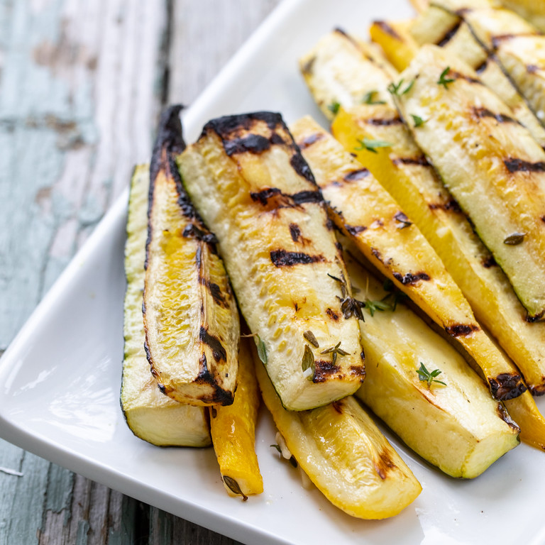 Grilled zucchini and summer squash on a platter.