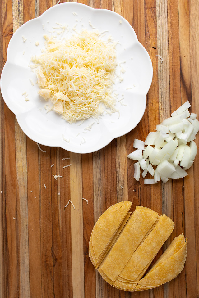 Plate of shredded cheese, diced onion and sliced tortillas.