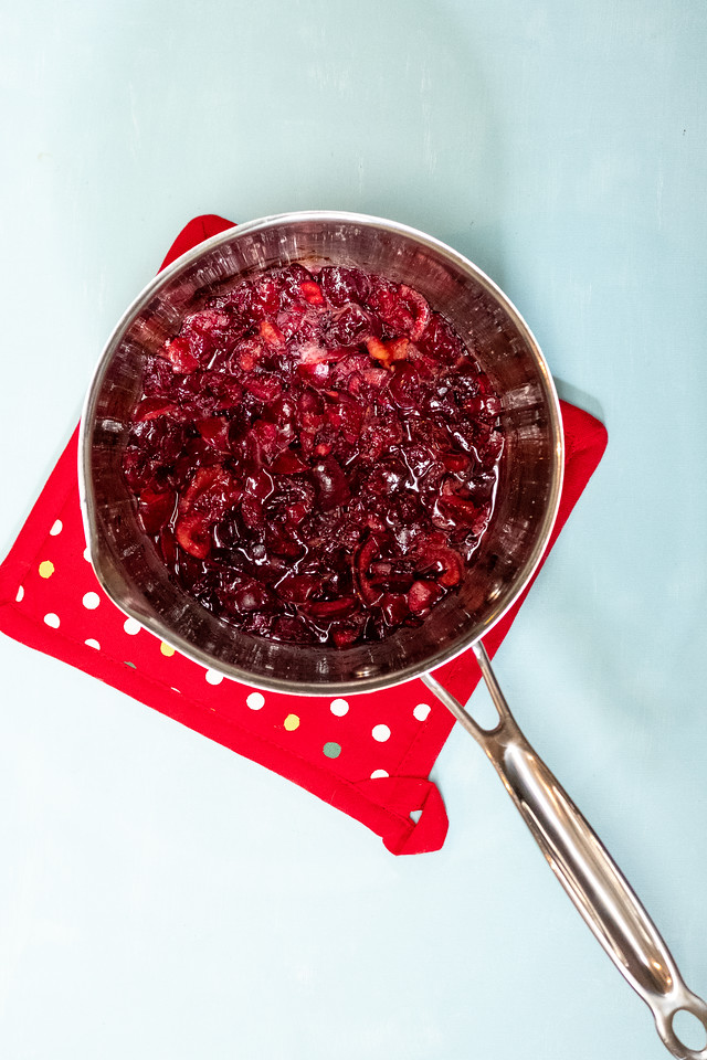 Cherries cooked down to a syrup in a pan.