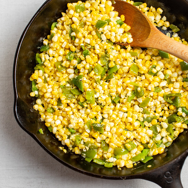 Corn with green bell peppers in a cast iron skillet.