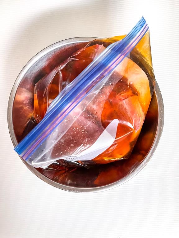Pork chops in a ziploc bag with a brown brining liquid.