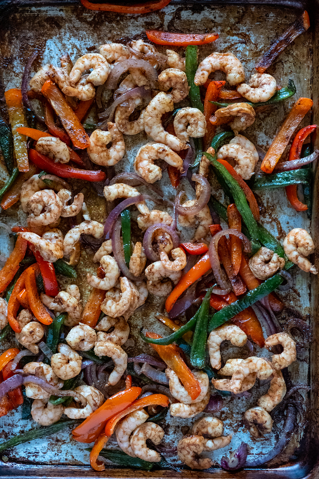 Baking sheet with shrimp and peppers.