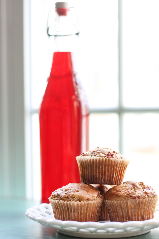 Plate of muffins with a bottle of cranberry liqueur behind them.