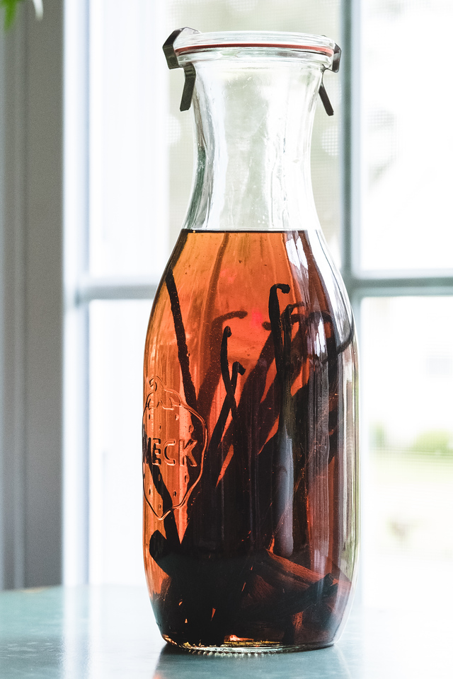 Bottle filled with brown liquid and vanilla beans