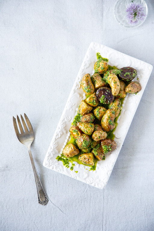 Platter of roasted fingerling potatoes tossed in a green chive pesto.