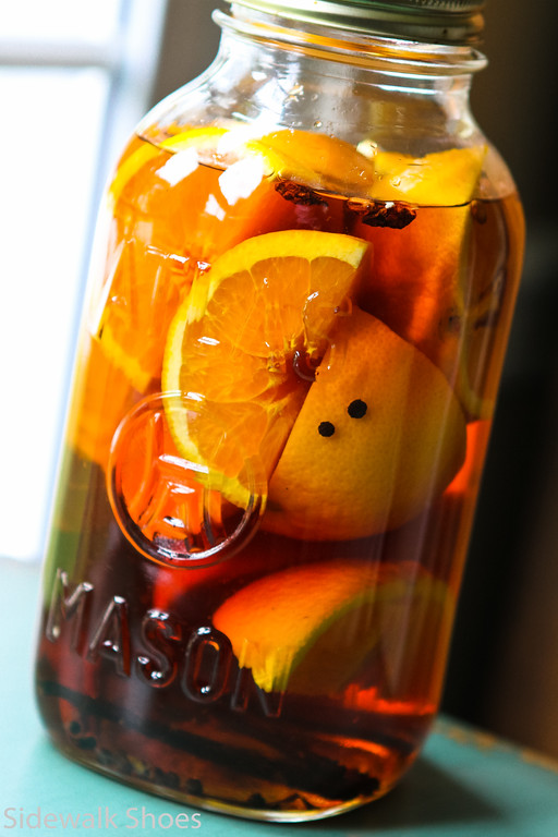 bottle of liquor filled with oranges and spices