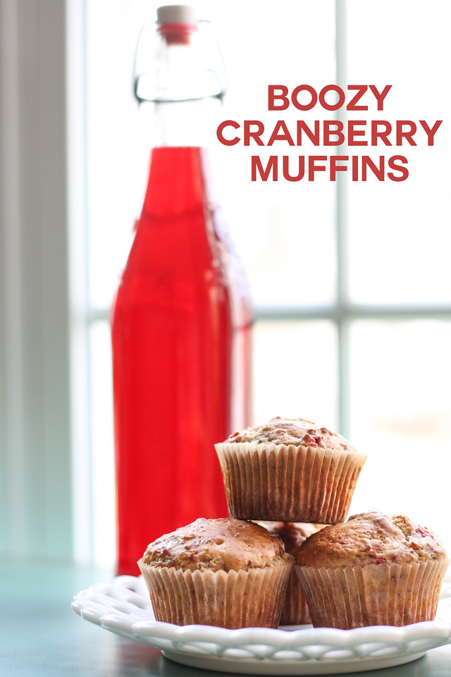 Plate of muffins with bottle of cranberry liqueur behind it and text overlay reading Boozy Cranberry Muffins.