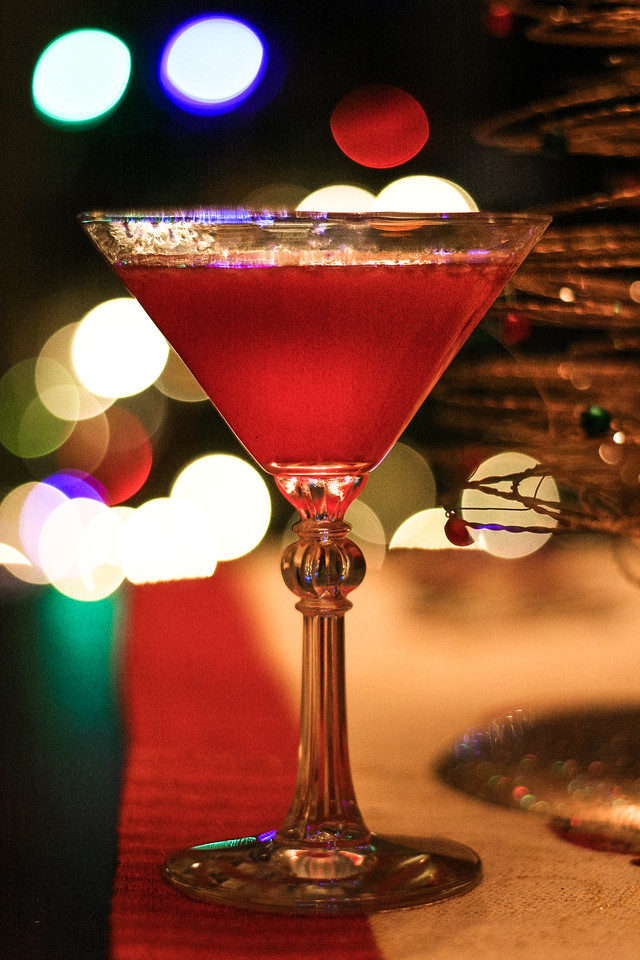 Cranberry cosmopolitan in a cocktail glass in front of Christmas tree