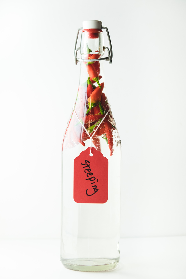 Bottle filled with clear liquid, red peppers and a steeping tag on the bottle