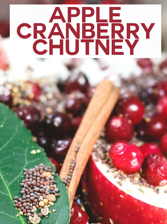 Apples, cranberries, cinnamon stick, spices with text overlay reading Apple Cranberry Chutney
