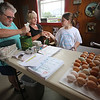 From left, customer Colleen Foley of Dracut buying two dozen eggs, Sandra Gervais of Tyngsboro (owner Anna Corey's sister-in-law), and Kaylee Plourde, 9, of Dracut, Corey's great-niece, washing eggs at Corey Pride Farm in Dracut, which raises grass-fed beef and free-range chickens. (SUN/Julia Malakie)