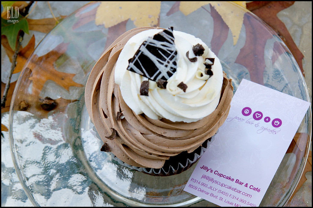 Chocolate Thunder - Jilly's Cupcake Bar & Cafe<br /> Cake: Chocolate<br />  Filling: : Dark chocolate ganache<br />  Topping:  Milk chocolate buttercream, vanilla buttercream, chocolate shavings, and chocolate bark