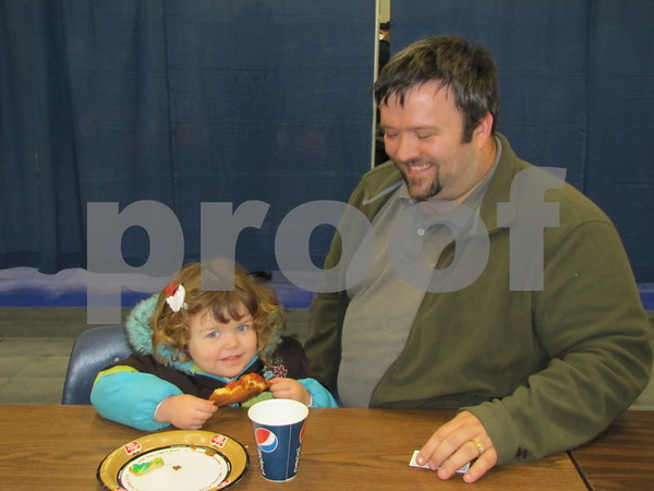 Olivia Schmidt and her dad, Mike Schmidt, enjoy pizza at the ICCC Food and Beverage Expo.