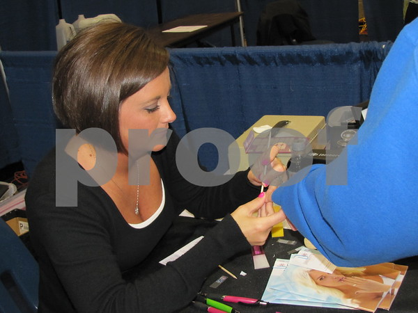 Abbie Laufensweiler in her booth for her business 'Jamberry Nails' demonstrates to an attendee.