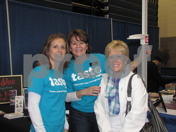 Fonda Nelson and Kim Shaeffer, personal trainers from Hy-Vee measured Diane Whittiers height at their booth at the vendor show.