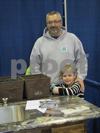 Dave Fogelman and Madeline Brockway pose in Fogelman's booth Custom Countertops of Iowa.