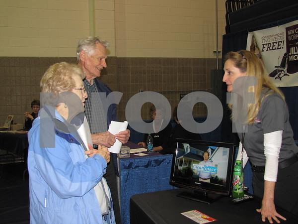 Mel and Marian Renken visit with Tascha Renken, their daughter, at her booth Thrasher Basements of Omaha.