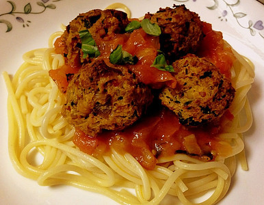 """Veggie """"meatballs"""" on marinara sauce on  bed of spaghetti."""