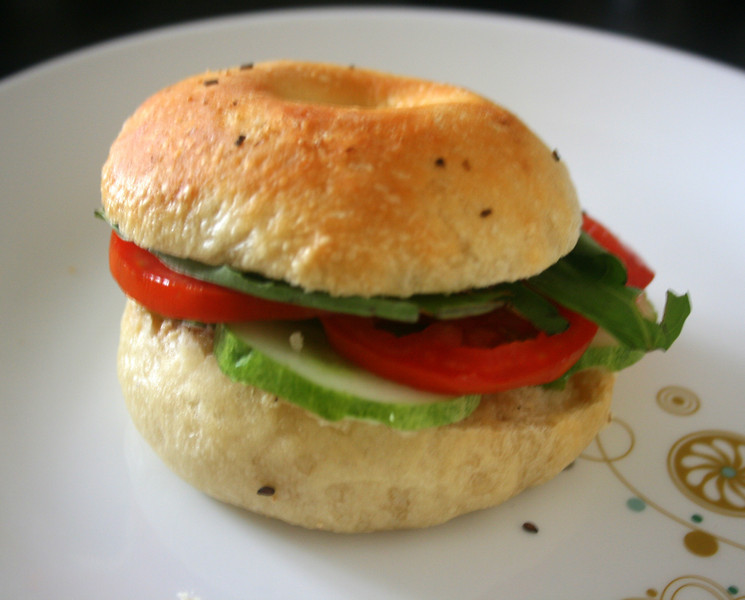 Instead of cream cheese, this bagel sandwich has homemade hummus, cucumber, tomatoes and basil.