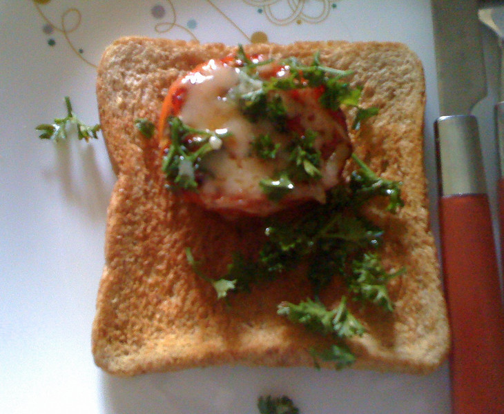 Grilled tomato topped with Gruyère and parsley on toast