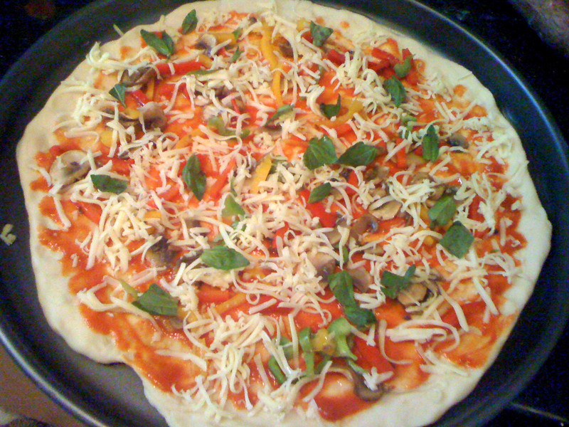 Pizza, topped with mushrooms and basil and peppers, ready for the oven