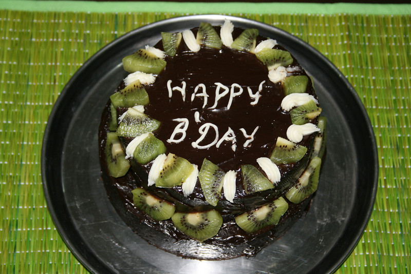 Chocolate fudge cake with topped with kiwis.