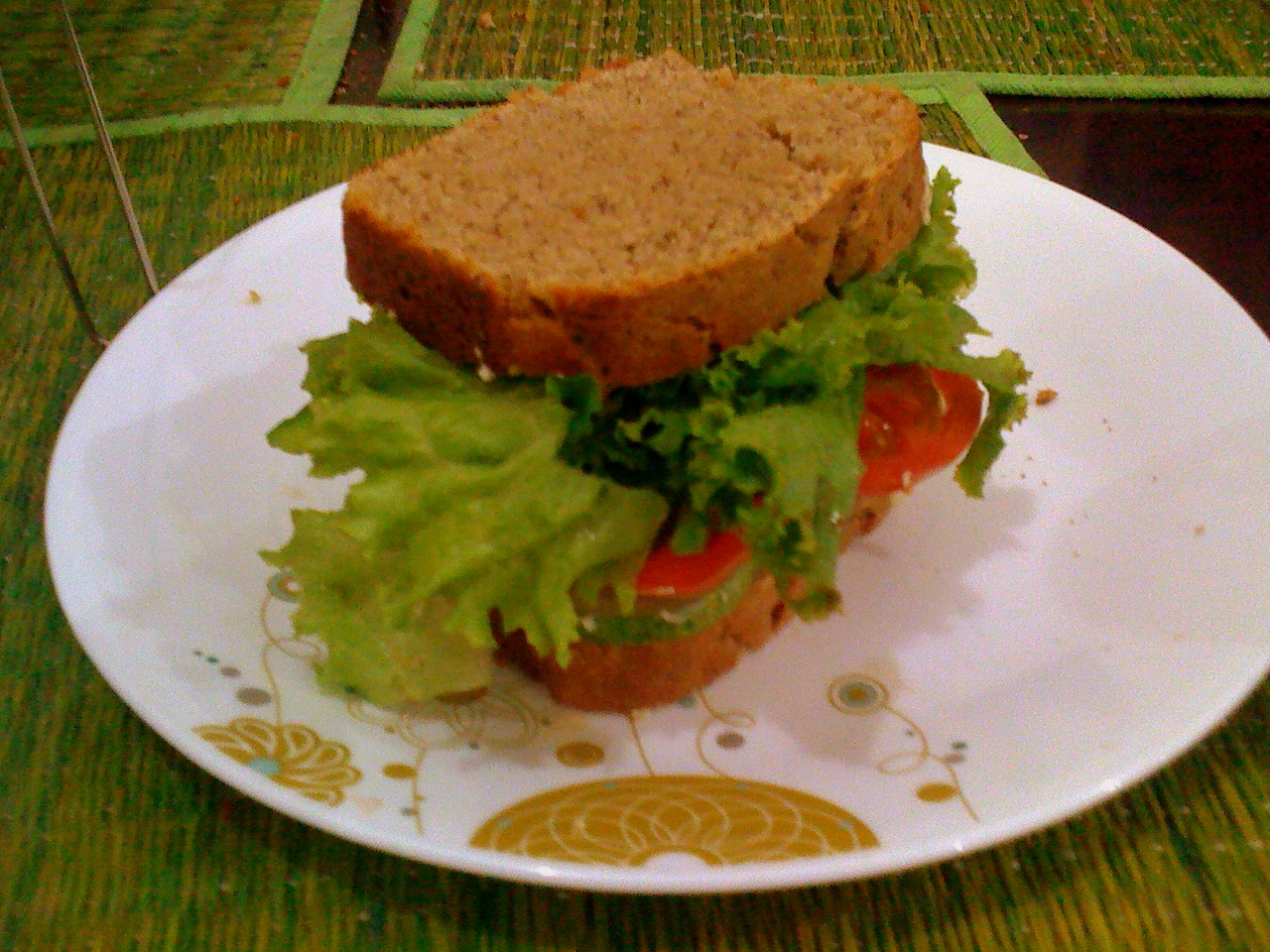 Lettuce tomatoes and cucumber in a sandwich, with above whole wheat bread.