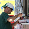 """Janet's Chili Dogs food truck on Water Street in Fitchburg, run by owner Debby Tecsi of Fitchburg. Ryan Barbin of Lunenburg adds condiments to his bacon cheese dog. He's a regular customer and says """"it's always delicious."""" (SUN/Julia Malakie)"""
