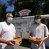 """Janet's Chili Dogs food truck on Water Street in Fitchburg, run by owner Debby Tecsi of Fitchburg. Justin Schutrick, left, and co-worker Jamie Laramee, right, both of Oxford, buy multiple Coney Island dogs for lunch. Working for New View Home Improvement, Schutrick said they discovered Janet's Chili Dogs when """"we had a job up here last year. Now every time we have a slow day, we drive up here."""" (SUN/Julia Malakie)"""
