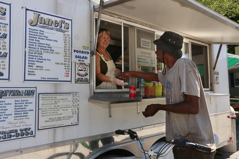 Janet's Chili Dogs food truck on Water Street in Fitchburg, run by owner Debby Tecsi of Fitchburg. Bo Burton of Leominster, a mechanic who works nearby, picks up a Coca Cola from Debby Tecsi. (SUN/Julia Malakie)