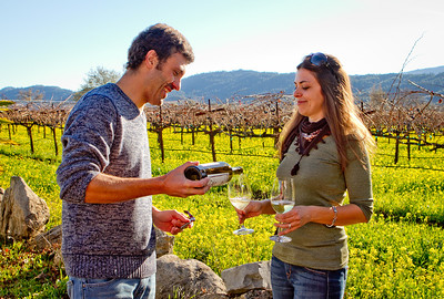 Enrico Bertoz pours some of their wine for his wife,  Letizia Pauletto of Arbe Garbe Winery in a vineyard next to their home in Rutherford, Calif., on Friday, December 16th,  2011.