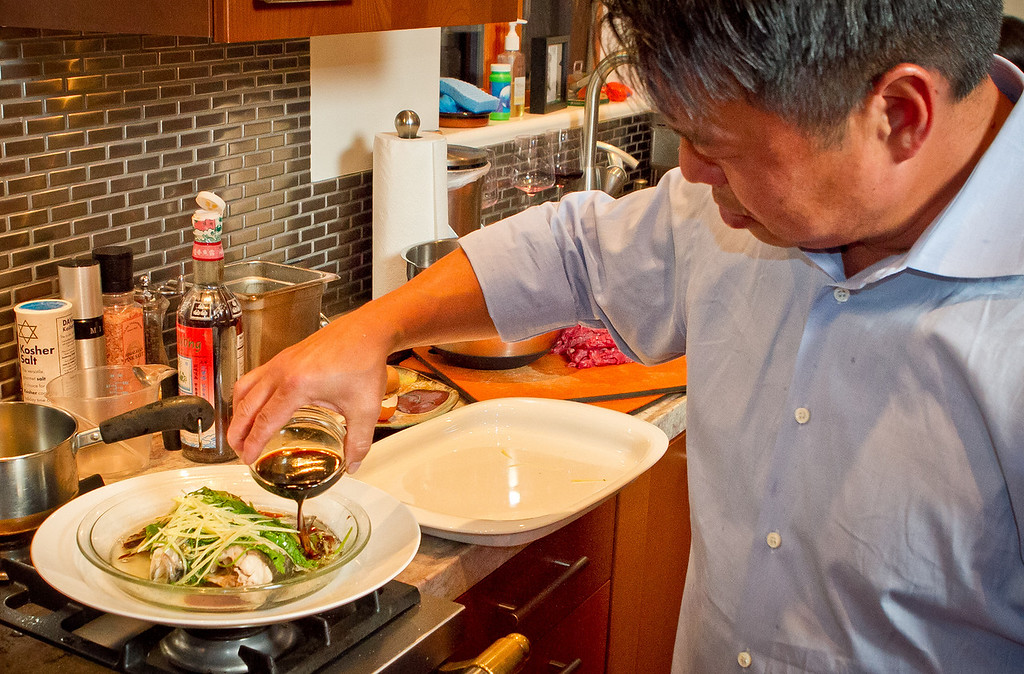 Chef Charles Phan pours soy sauce over a steamed whole fish at a home in Mill Valley on Tuesday, September 11th, 2012.