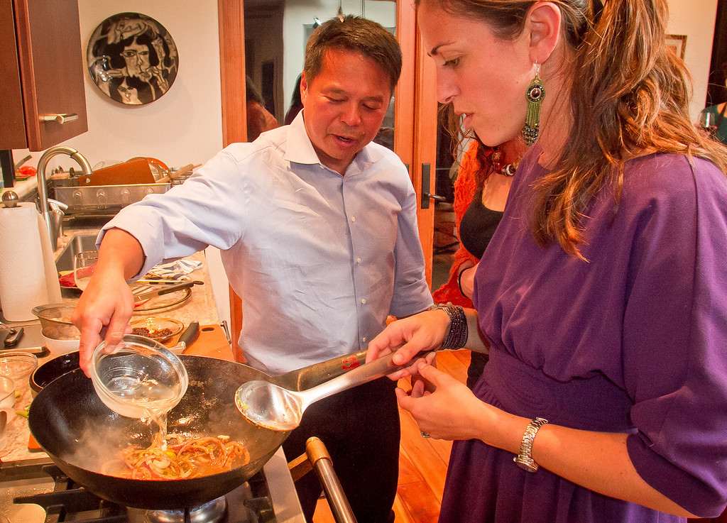 Chef Charles Phan adds oil to a wok as he helps Shira Weisman at her home in Mill Valley on Tuesday, September 11th, 2012.