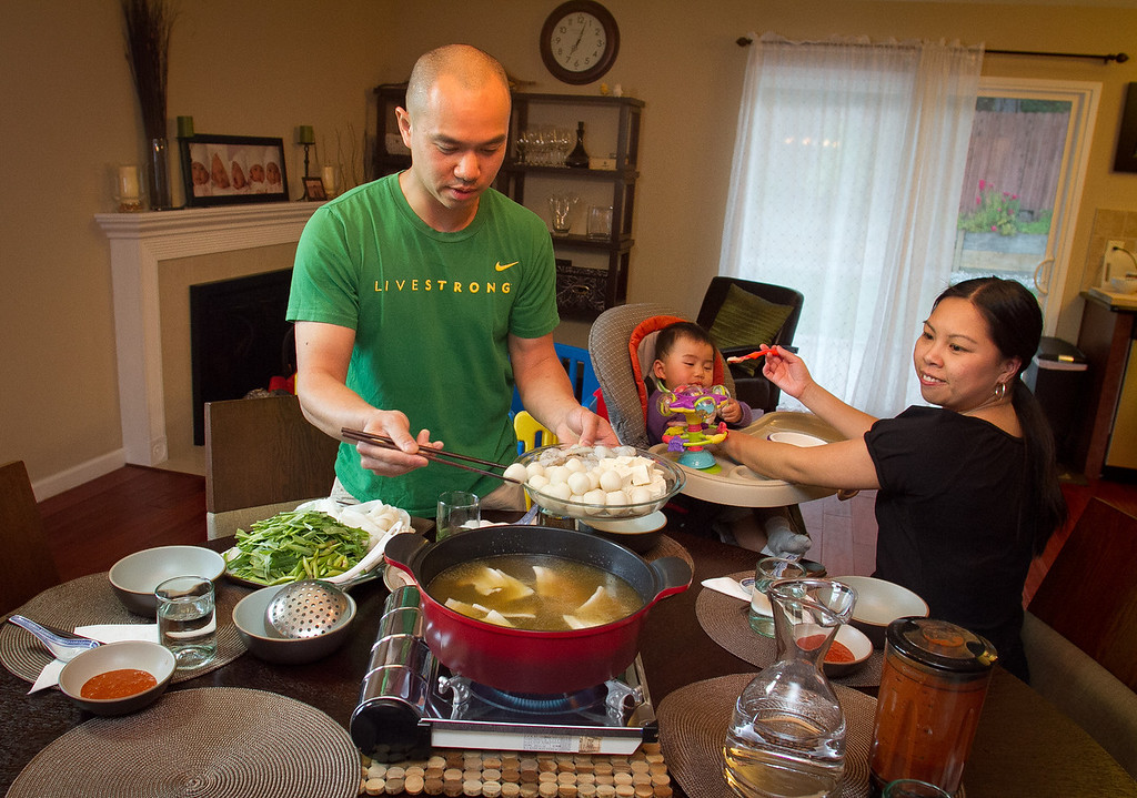 Chef James Syhabout of Commis puts fish balls in the Thai Hot Pot while Stacy Ly feeds their baby, Emma Syhabout at their home in Oakland, Calif., on Tuesday, May 1st, 2012.