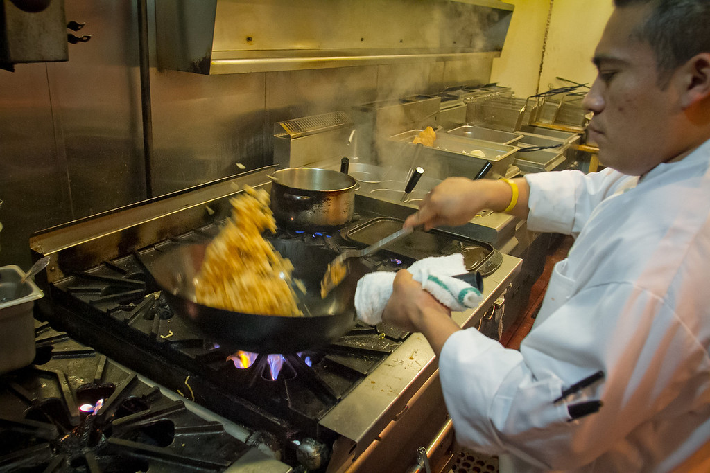 A cook prepares Pork Belly Fried Rice at Chubby Noodles within Amante Bar in San Francisco, Calif., on Saturday, February 25th, 2012.