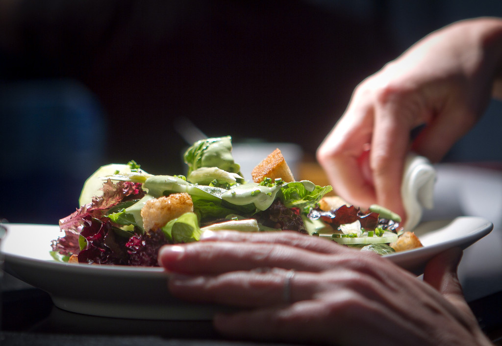 A server cleans the plate on the Baby Greens Salad at Claudine Restaurant in San Francisco, Calif., on Monday, March 5th, 2012.