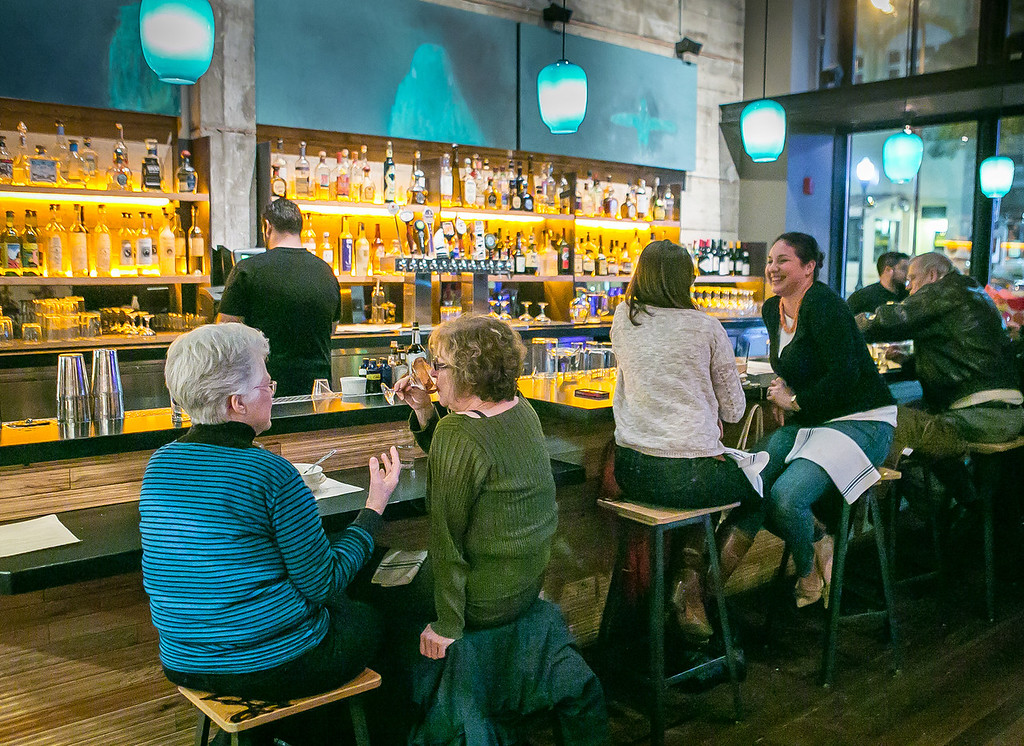 People enjoy cocktails during happy hour in the front bar at Comal restaurant in Berkeley, Calif., on Thursday, January 10th, 2013.