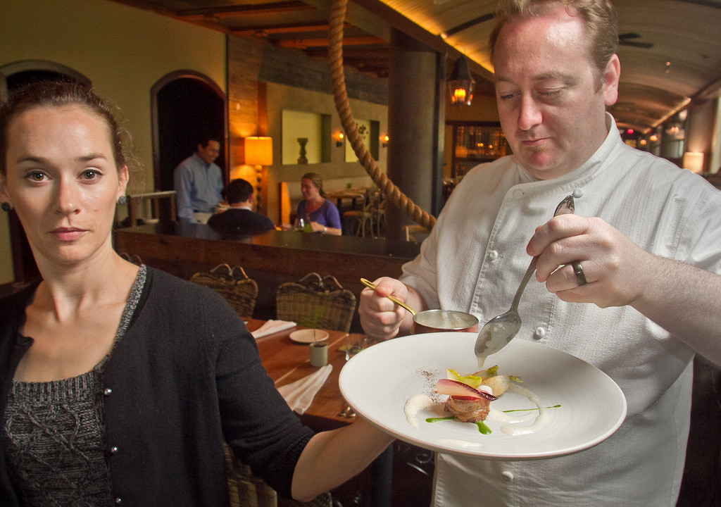 Assistant Meghan Rand holds the Lamb entree while chef Joseph Humphrey sauces the dish at Dixie Restaurant in San Francisco, Calif., on Friday, August 3rd, 2012.