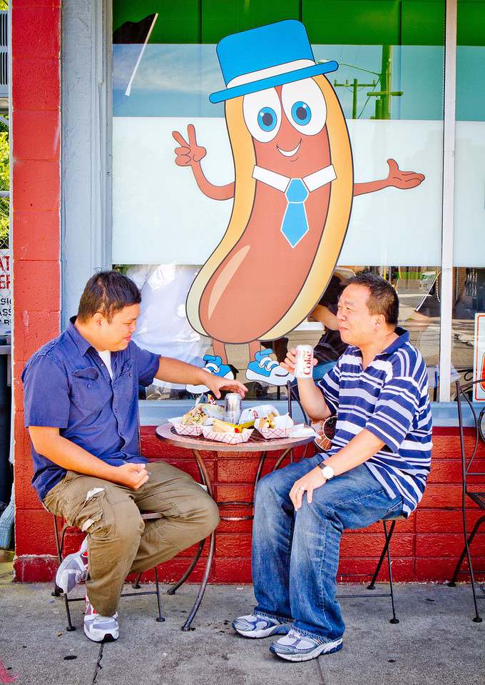 Elton Wong, (right), and Tan Ngyuen enjoy hot dogs outside of Doggy-Style Hot Dogs in Alameda, Calif. on Thursday, August 9th,  2012.