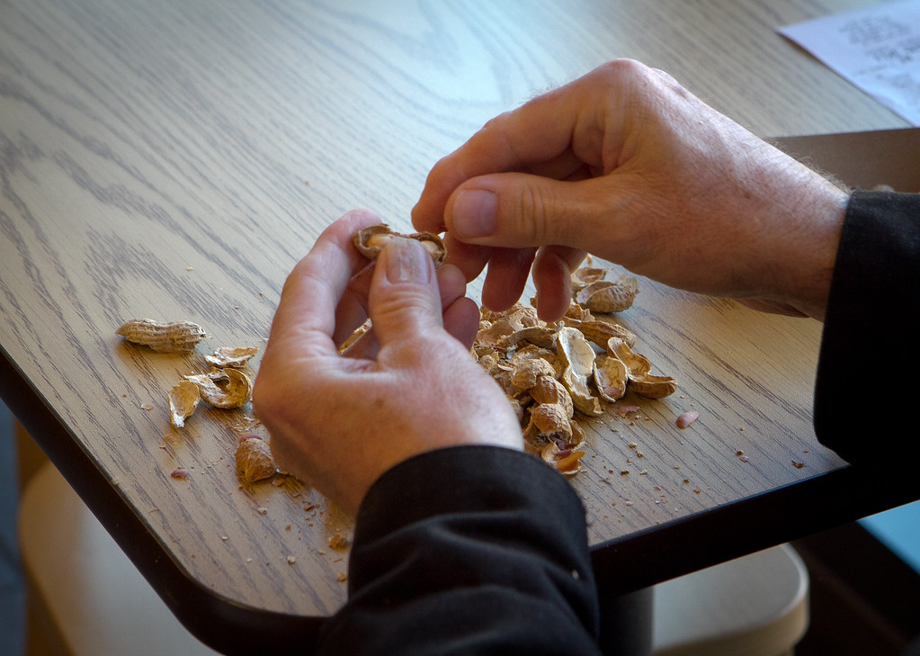 A customer shells peanuts wile waiting for his burger at Five Guys Burgers in Burlingame, Calif., on Thursday, February 2, 2012.