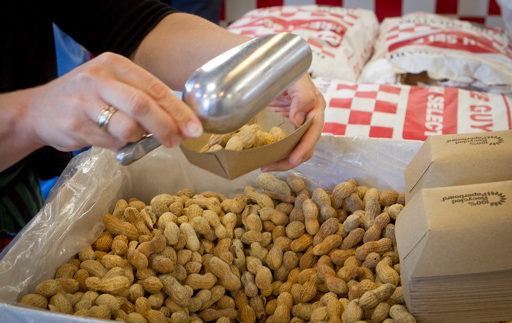 A customer grabs some peanuts while in line at Five Guys Burgers in Burlingame, Calif., on Thursday, February 2, 2012.