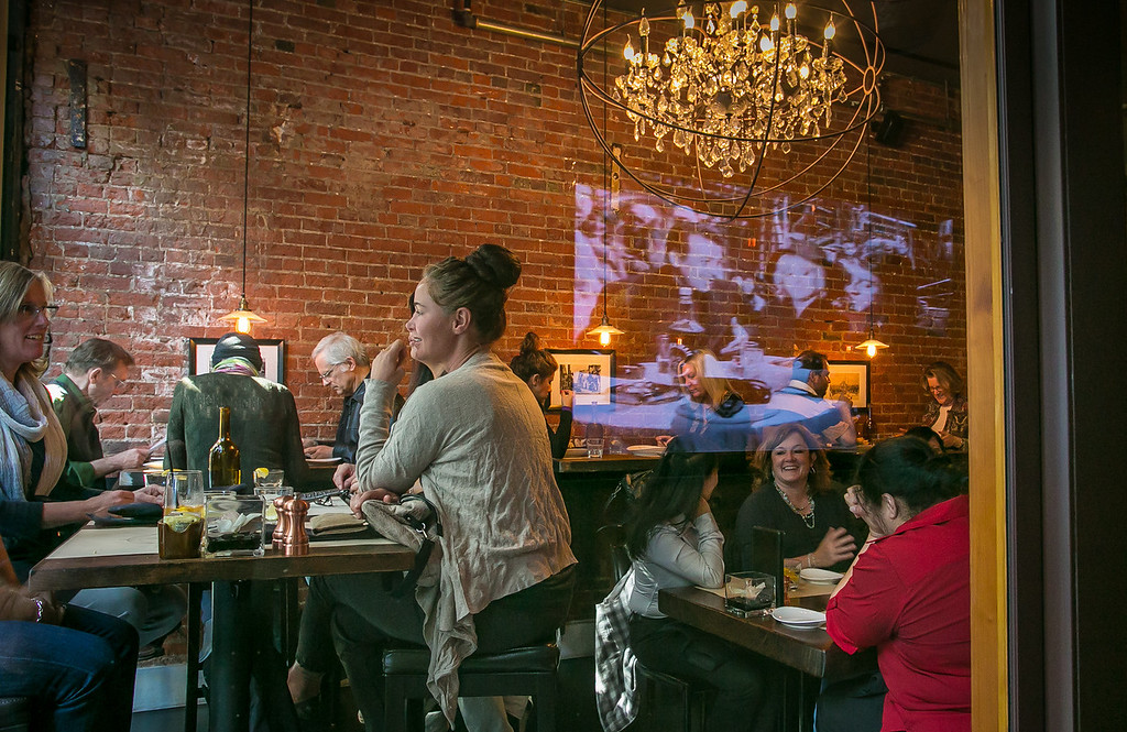 Diners enjoy lunch with the reflection of the big screen TV   at Machka restaurant in San Francisco, Calif. ion Monday, February 25th 2013.