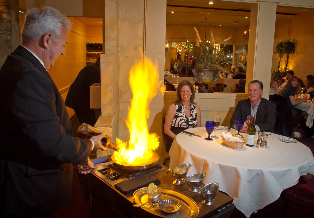 Dimitrios Papas makes Steak Diane tableside for Bob and Kimra Hulgan at the Iron Gate restaurant in Belmont , Calif., on Wednesday, May 2nd, 2012.