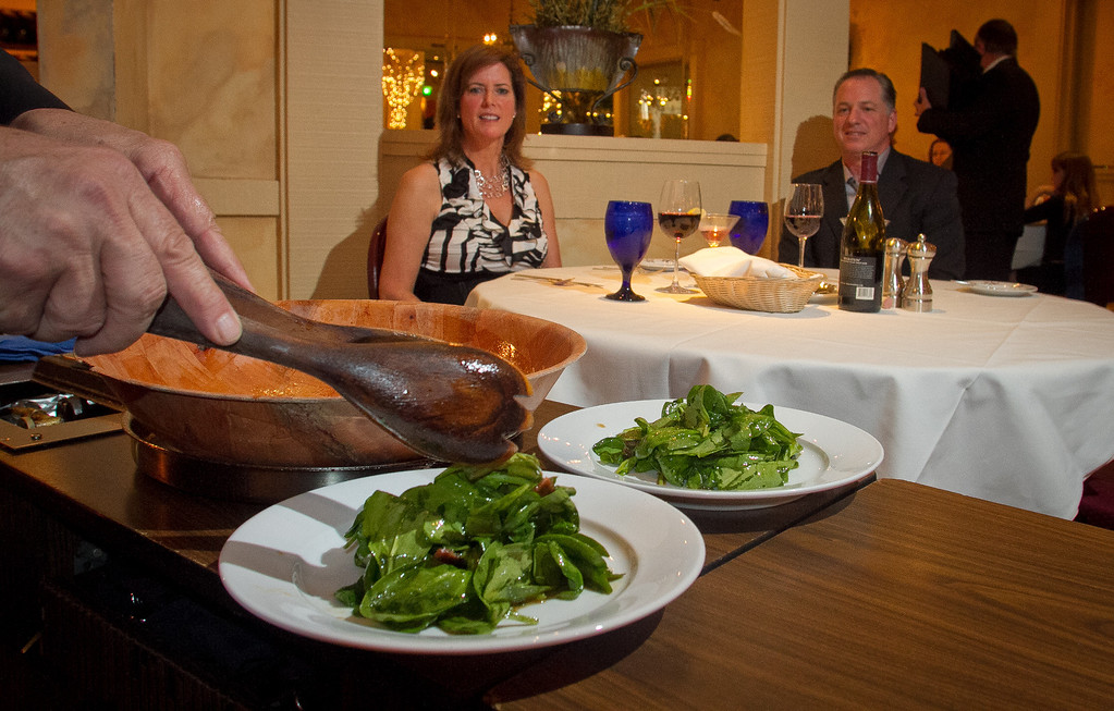 Dimitrios Papas serves a Spinach salad tableside for Nob and Kimra Hulgan at the Iron Gate restaurant in Belmont , Calif., on Wednesday, May 2nd, 2012.