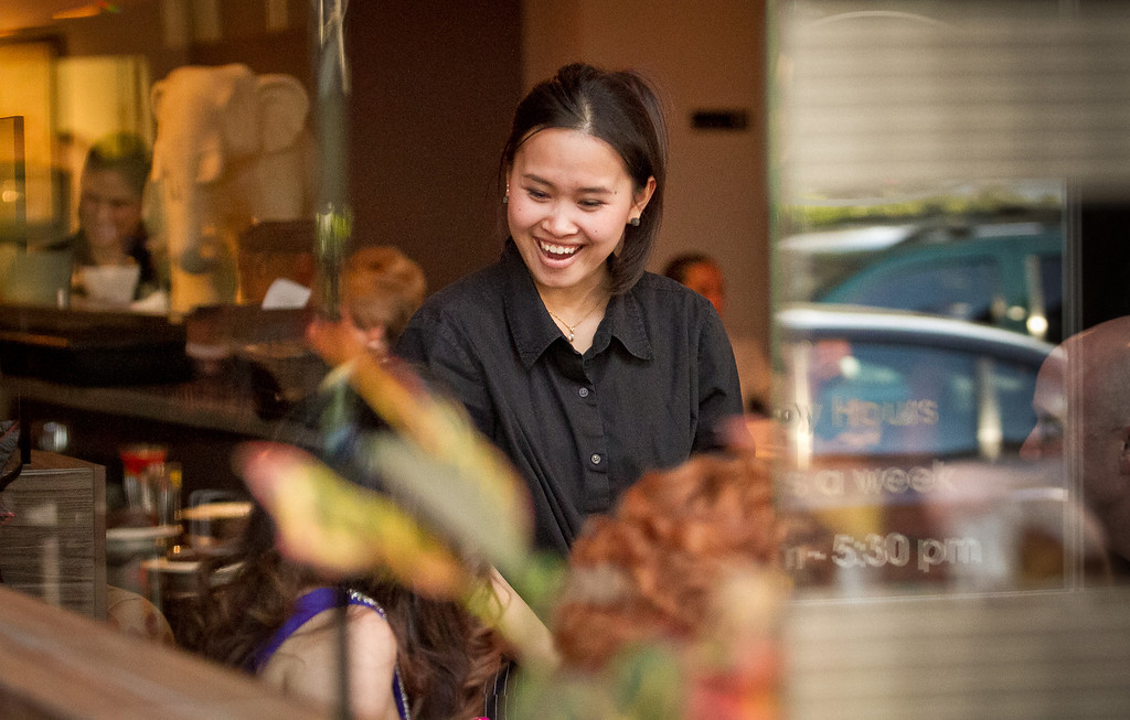 A server smiles at customers during dinner at Kacha Thai Bistro in Walnut Creek, Calif., on Friday April 7th, 2012.